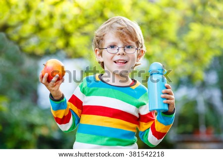 Funny little boy with apple and drink bottle on his first day to elementary school or nursery. Outdoors.  Back to school, kids, lifestyle concept - stock photo
