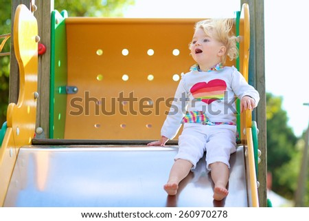 Funny little child, adorable preschooler girl in pretty dress having fun on a slide in the park on summer day - stock photo