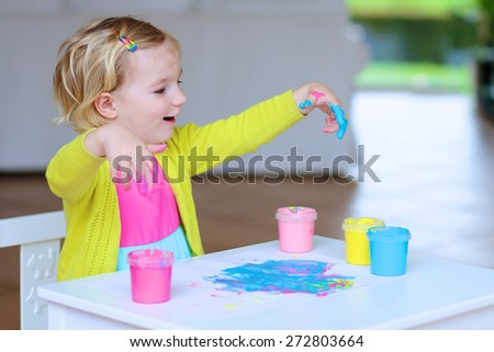 Funny little child, blonde artistic toddler girl painting with colorful finger paints indoors at bright room at home or kindergarten  - stock photo