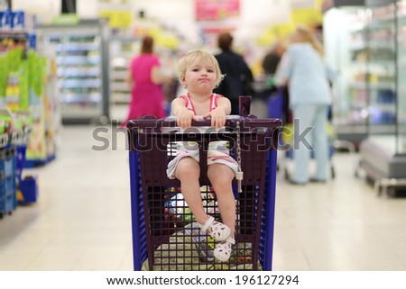 Funny little child, blonde toddler girl, sitting in the trolley during family shopping in hypermarket - stock photo