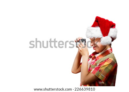 Funny little child dressed as Santa taking photo with camera smiling. Christmas concept.  - stock photo