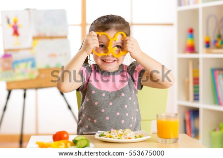 Funny little child eats healthy food in nursery room