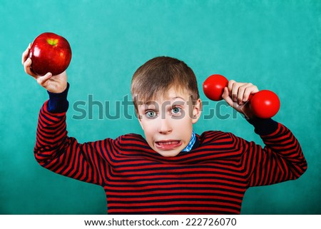 Funny little child holding red dumbbell and apple with funny expression  - stock photo