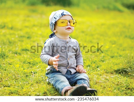 Funny little child in sunglasses outdoors on the grass summer - stock photo