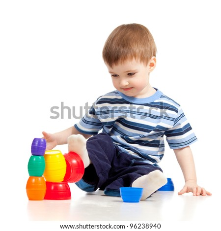 Funny little child is playing with color toys, isolated over white - stock photo