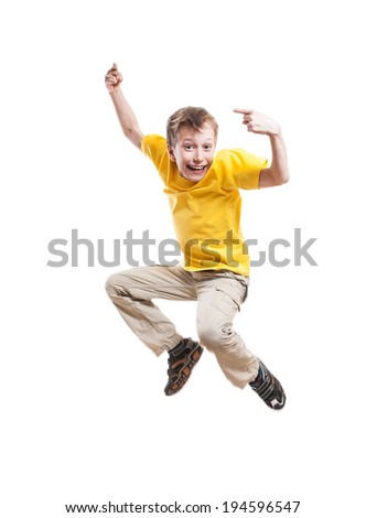 Funny little child jumping and laughing pointing with his index finger over white background