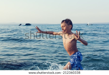 Funny little child playing in the sea at sunset. Summer vacation concept.  - stock photo