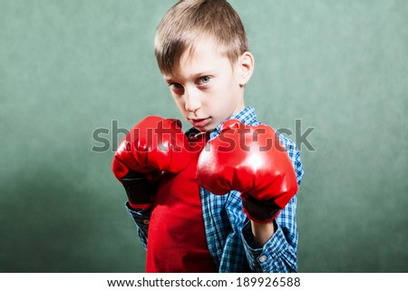 Funny little child wearing red boxer gloves fighting with funny expression