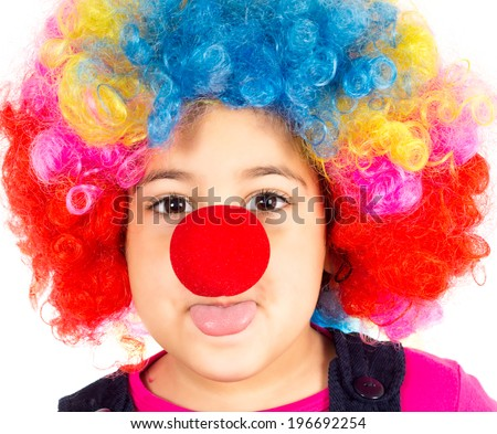 Funny little child with clown wig and red nose mocking  - stock photo