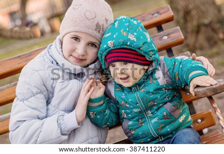 funny little children brother and sister sitting on bench