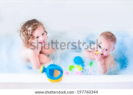 Funny little girl and her cute baby brother having fun taking bath together playing in water with foam with colorful toys after shower  - stock photo