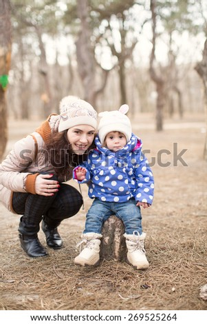 Funny little girl and mother in spring forest