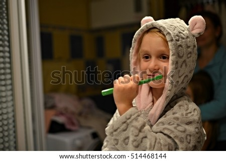 Funny little girl brushing teeth in bath.