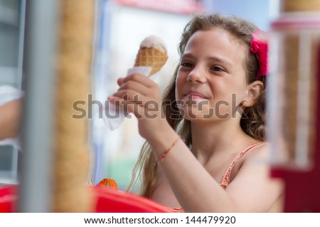 Funny little girl buying an ice cream outdoors - stock photo