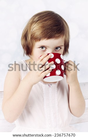 Funny little girl drinking hot chocolate