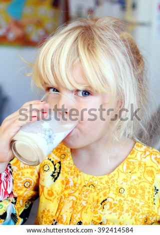 Funny little girl drinking milk. Healthy breakfast.