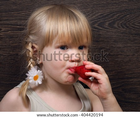 Funny little girl eating a strawberry. Portrait, face close. Blond hair, pigtails. Strawberries ripe, red. Girl grubby and rather