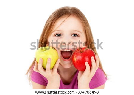 Funny little girl eating apple - stock photo