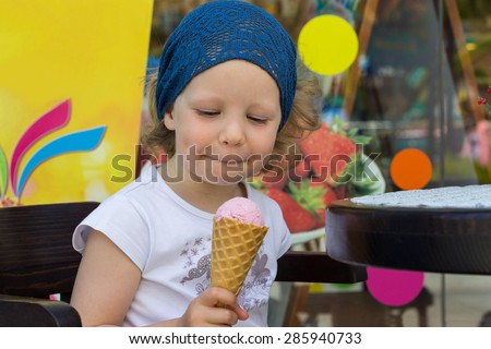 Funny little girl eating ice cream. Selective focus.