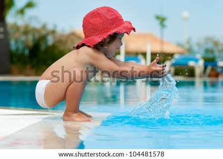 Funny little girl have a fun with a splash near swimming pool - stock photo