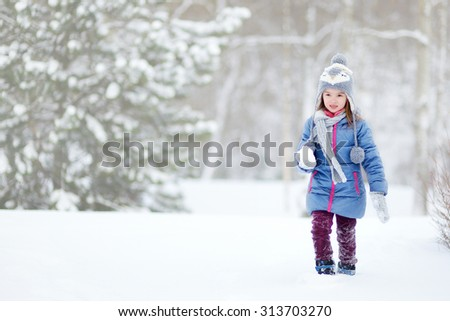 Funny little girl having fun in beautiful winter park during snowfall - stock photo