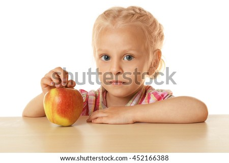 Funny little girl hiding behind  table and looking at apple - stock photo