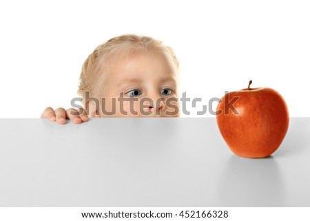 Funny little girl hiding behind white table and looking at apple - stock photo