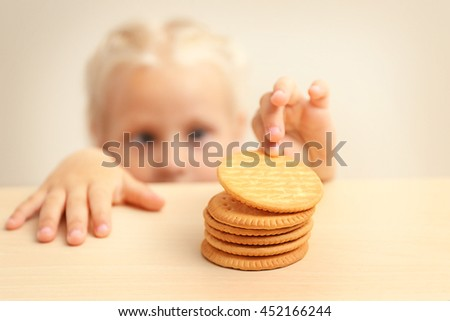 Funny little girl hiding behind white table and looking at pile of cookies - stock photo