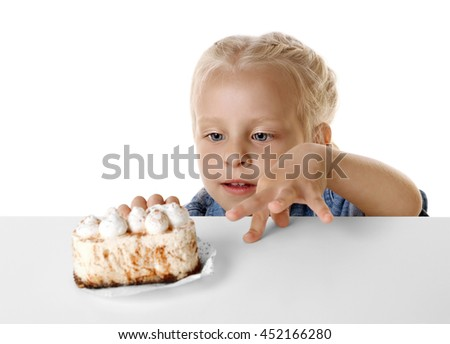 Funny little girl hiding behind white table and looking at tasty cake - stock photo