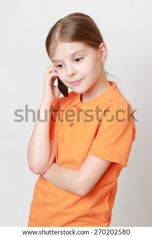 Funny little girl holding mobile phone and talking - stock photo