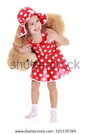 Funny little girl in a short red summer dress with white polka dots and matching bonnet, holds on his shoulders a large Teddy bear . the girl is on the floor in white socks -Isolated on white - stock photo
