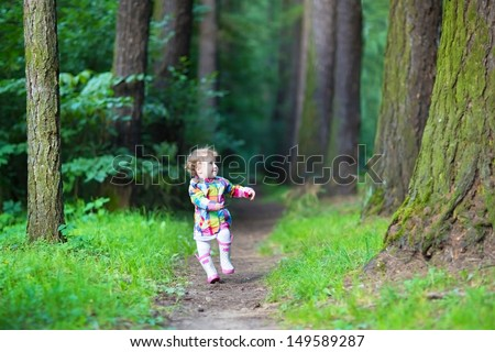 Funny little girl in rain boots walking in a park
