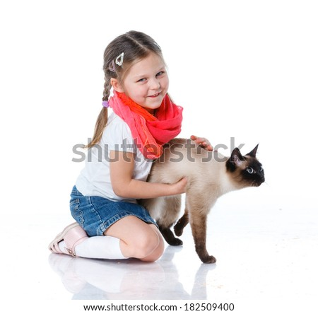 Funny little girl kid playing with cat. Isolated on white background. - stock photo