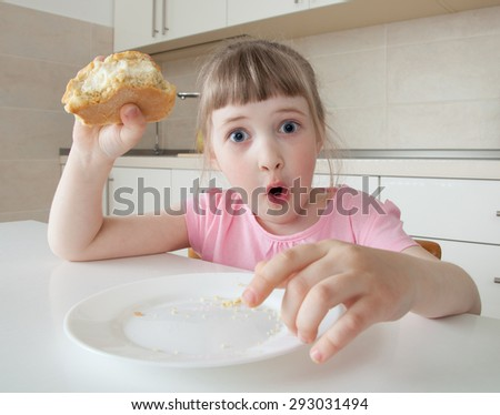 Funny little girl looking in wide-eyed astonishment and holding a pie - stock photo