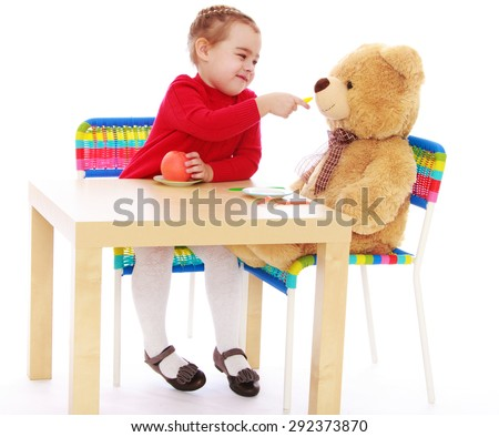 Funny little girl playing a game my little sister , she's feeding spoon Teddy bear - isolated on white background - stock photo