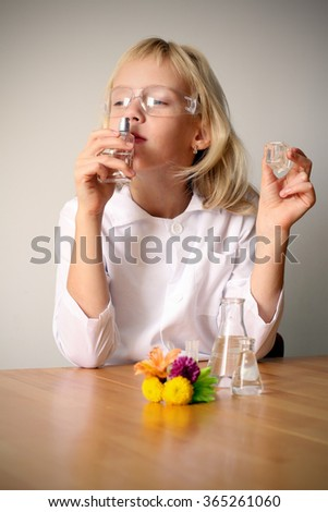 Funny little girl playing perfume chemistry.  - stock photo