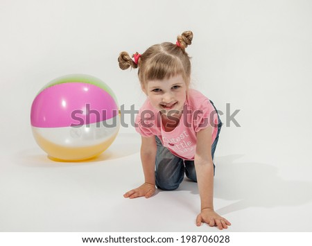 Funny little girl playing with ball, white background - stock photo