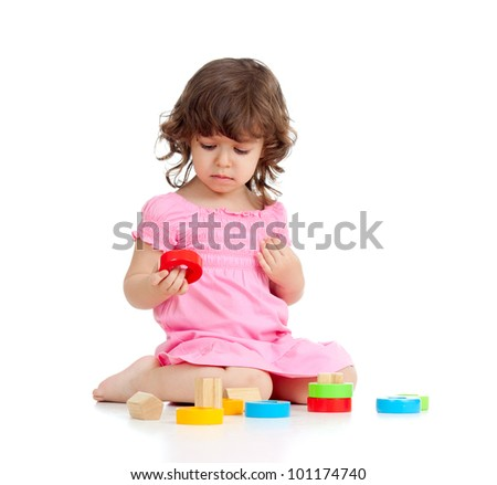 Funny little girl playing with cup toys, isolated over white
