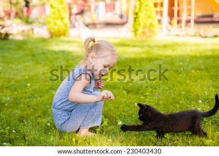 funny little girl playing with kitten - stock photo