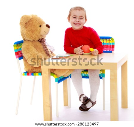 Funny little girl playing with Teddy bear sitting at the table-isolated on white background