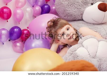 Funny little girl posing lying on big plush bear - stock photo