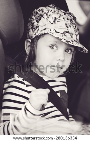 funny little girl sitting  in the  car - stock photo