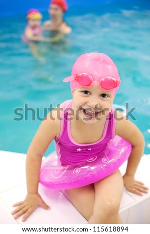 Funny little girl sitting near  swimming  pool in an pink life preserver - stock photo