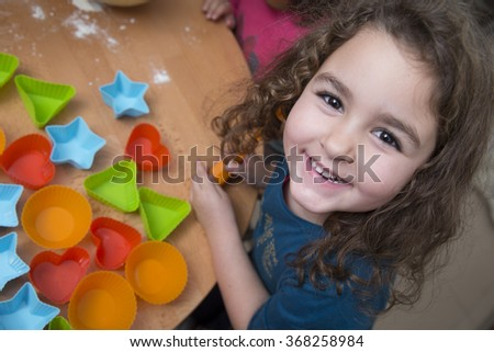 Funny little girl smiling while looking at camera - stock photo