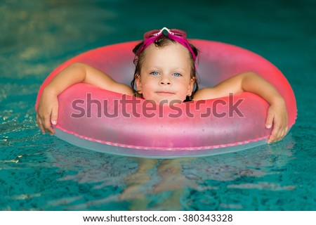 Funny little girl swimming in a pool in pink life preserver - stock photo