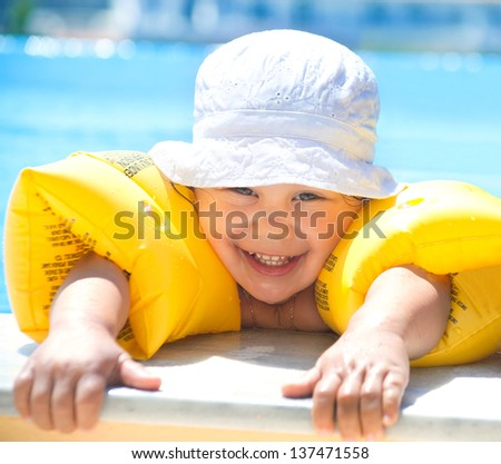 Funny little girl swims in a pool in yellow inflatable armbands - stock photo
