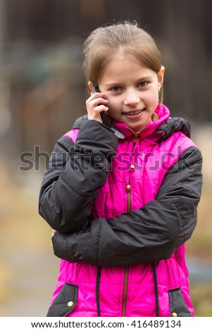 Funny little girl talking on the phone, outdoors portrait. - stock photo