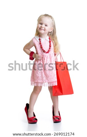 Funny little girl trying her mom's red accessories and shoes on - stock photo