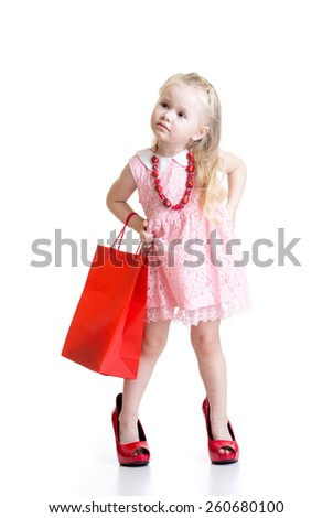 Funny little girl trying on her mother accessories and shoes isolated on white background - stock photo