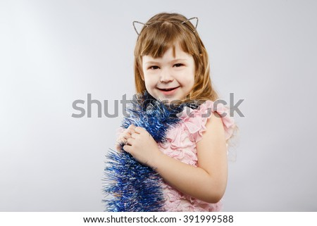 Funny little girl wearing pink dress, metal cat ears and blue festoon looking right at camera, gray studio background, copy space, portrait. - stock photo
